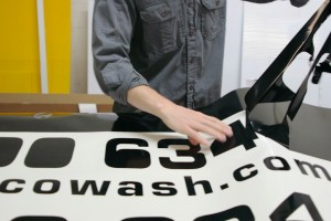Weeding black vinyl lettering by hand